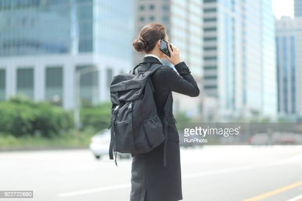 Businesswoman in back pack talking on smartphone in city street