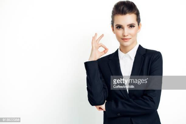 Zakenvrouw in zwart pak duimen geïsoleerd op wit