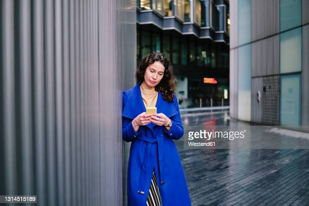 businesswoman in blue trench coat working on mobile phone while leaning on wall - grey colour stock pictures, royalty-free photos & images