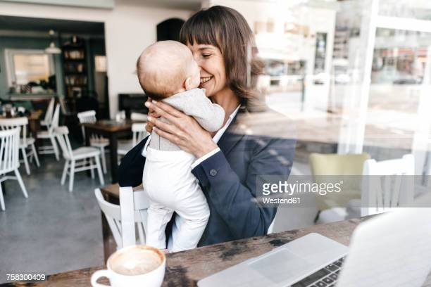 businesswoman in cafe holding baby - baby human age stock pictures, royalty-free photos & images