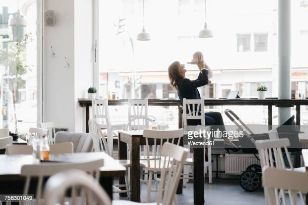 Businesswoman in cafe holding her baby aloft