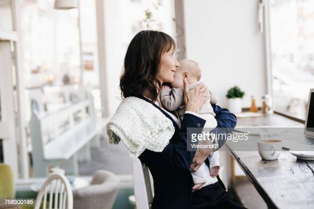 Businesswoman in cafe kissing her baby