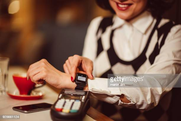 businesswoman in cafe paying contactless - nfc stock pictures, royalty-free photos & images