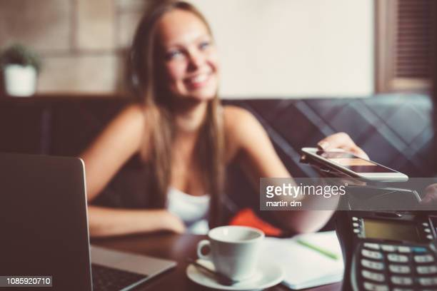 businesswoman in cafe paying contactless with smartphone - nfc stock pictures, royalty-free photos & images