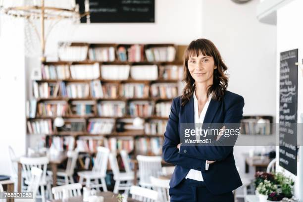 Businesswoman in cafe with arms crossed. looking at camera