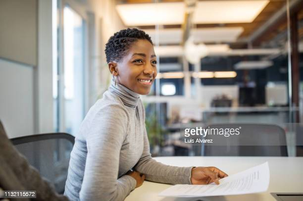 businesswoman in casuals working in office - business finance and industry stock pictures, royalty-free photos & images