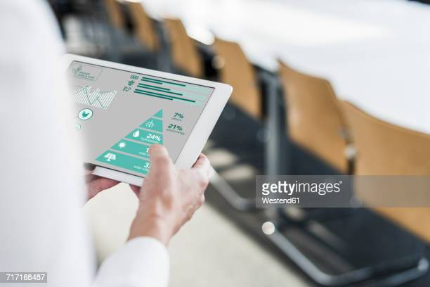 Businesswoman in conference room using tablet with data