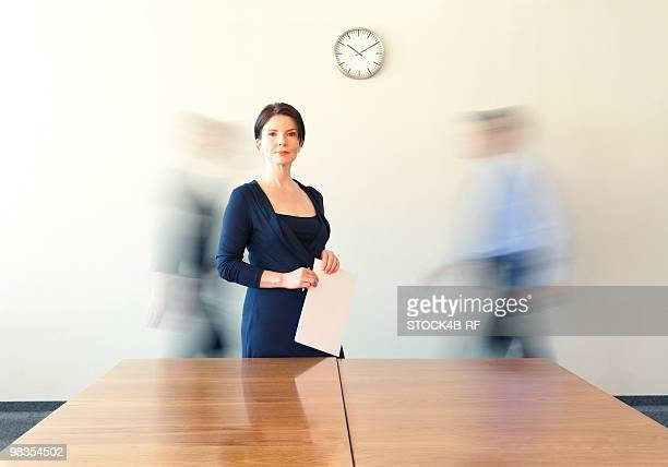 Businesswoman in conference room with people in background passing by