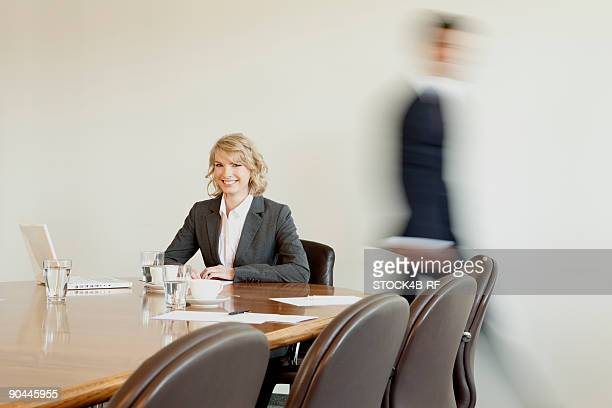 businesswoman in conference room with person in background passing by, munich, bavaria, germany - incidental people stock pictures, royalty-free photos & images