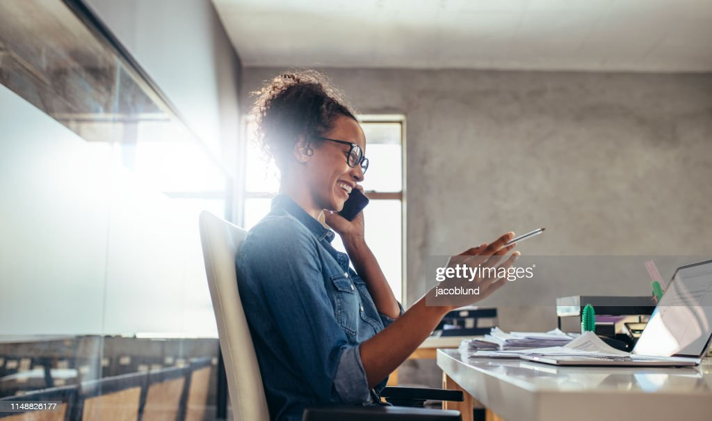 Businesswoman in conversation over phone : Stock Photo