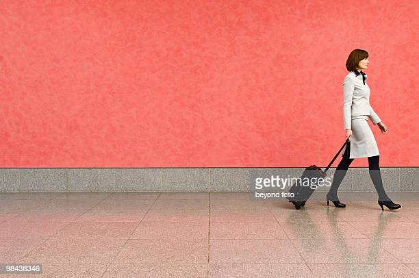 businesswoman in corridor pulling carry-on suitcase