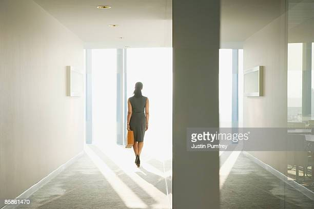 businesswoman in corridor, rear view - leaving stock pictures, royalty-free photos & images