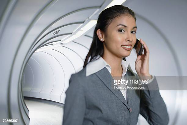 businesswoman in corridor using her mobile phone - passenger boarding bridge stock pictures, royalty-free photos & images