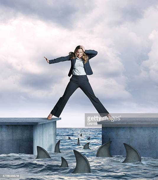 Businesswoman In Danger Of Falling Into Shark Infested Waters