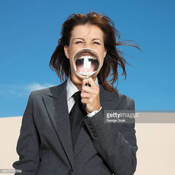 businesswoman in desert holding magnifying glass, portrait
