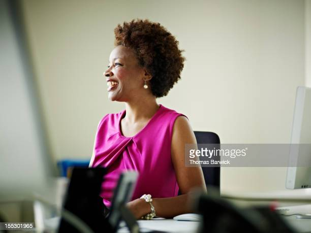 businesswoman in discussion at workstation smiling - abito senza maniche foto e immagini stock