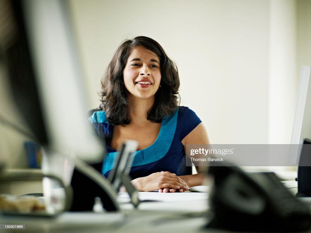 Businesswoman in discussion in office smiling : ストックフォト