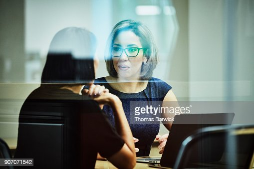 Businesswoman in discussion with client in office conference room