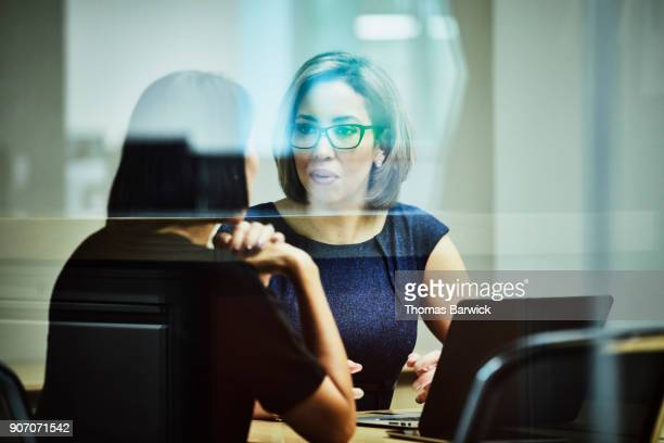 businesswoman in discussion with client in office conference room - advice stock pictures, royalty-free photos & images