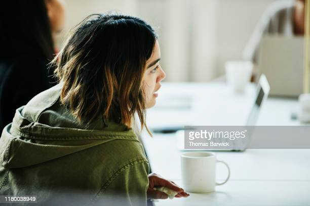 businesswoman in discussion with colleague during meeting in coworking office - filipino ethnicity and female not male fotografías e imágenes de stock