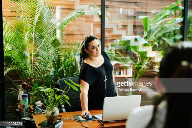 Businesswoman in discussion with coworker while working on laptop in office