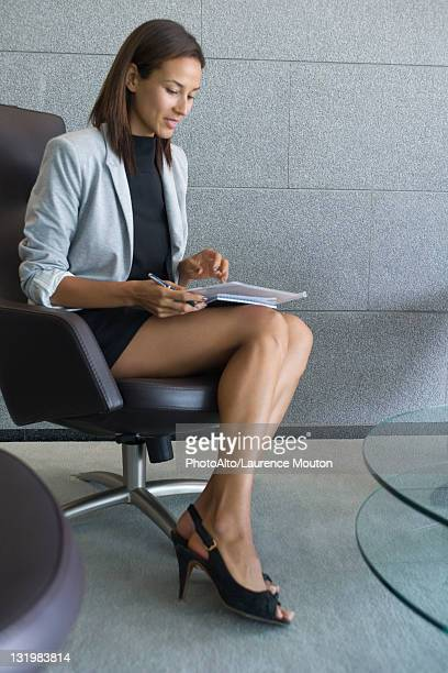 businesswoman in dress - legs and short skirt sitting down stock pictures, royalty-free photos & images