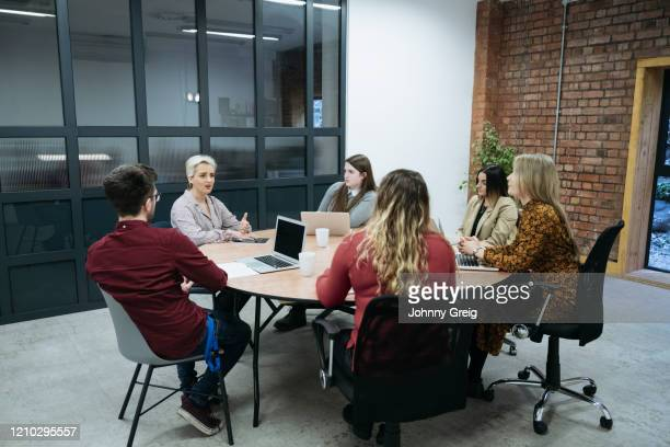 businesswoman in early 40s holding meeting with colleagues - femalefocuscollection stock pictures, royalty-free photos & images