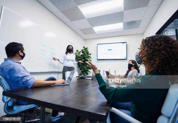 businesswoman in face mask giving presentation in office - chief executive officer stock pictures, royalty-free photos & images