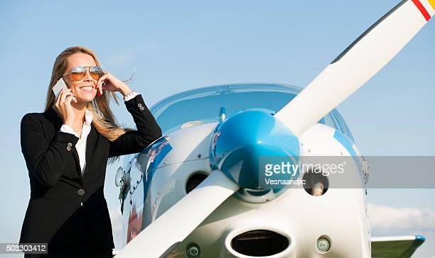 Businesswoman in front of private jet airplane