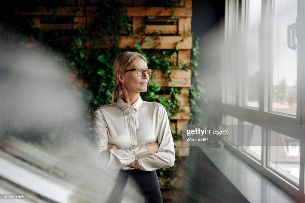 Businesswoman in green office looking out of window : Stock Photo