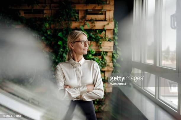 businesswoman in green office looking out of window - zakenvrouw stockfoto's en -beelden