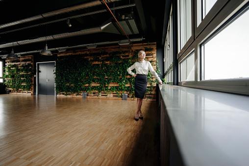 Businesswoman in green office looking out of window - gettyimageskorea