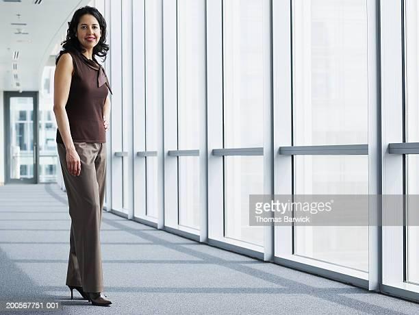 Businesswoman in hallway, smilng