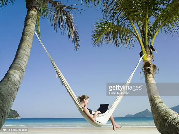 Businesswoman in hammock using laptop