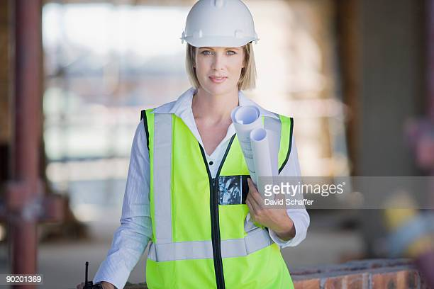 Businesswoman in hard-hat and safety vest holding blueprints