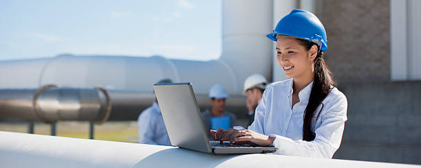 Businesswoman in hard-hat using laptop outdoors