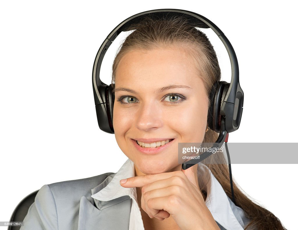 Businesswoman in headset sitting on chair, hand under chin : Stock Photo