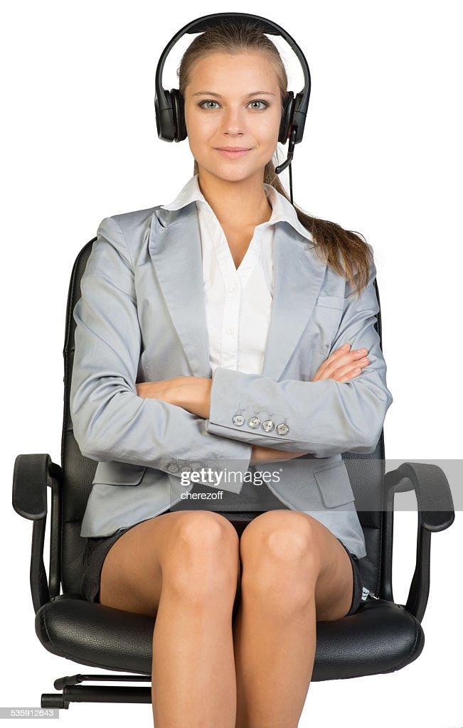 Mulher de negócios com auscultadores com microfone sentado na cadeira de escritório, seus Braços Cruzados : Foto de stock