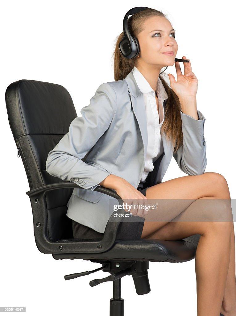 Mulher de negócios com auscultadores com microfone sentado na cadeira de Escritório : Foto de stock