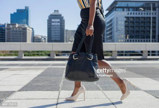 businesswoman in high heels walking through the city with her purse in hand. - black purse stock pictures, royalty-free photos & images