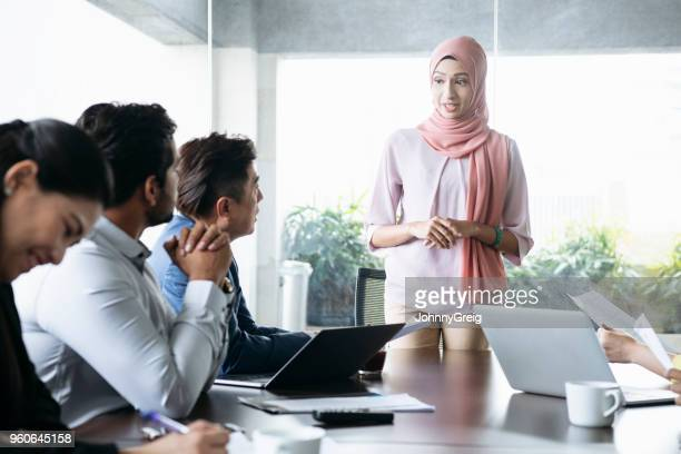 businesswoman in hijab listening to male colleague - malay hijab stock photos and pictures