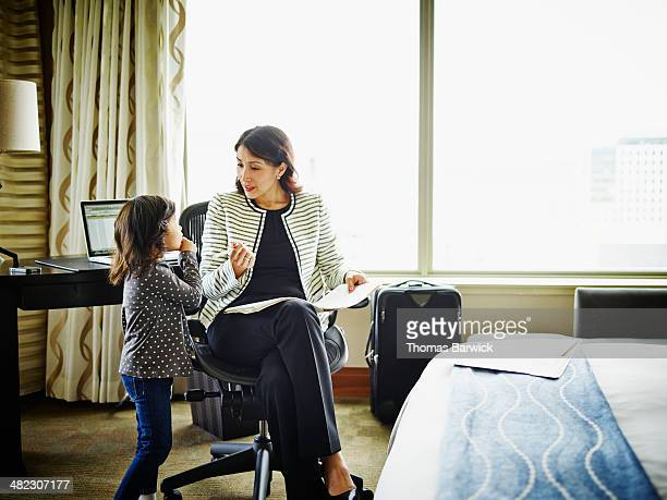 Businesswoman in hotel room talking to daughter