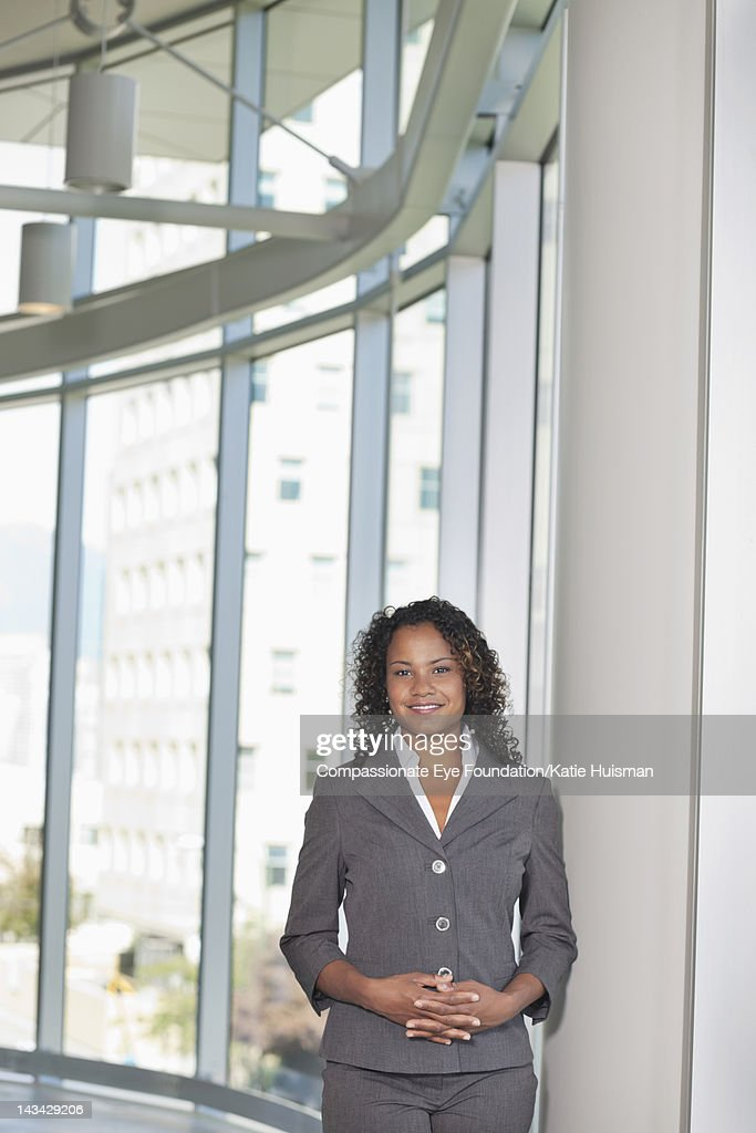 Businesswoman in lobby, smiling : Stock Photo