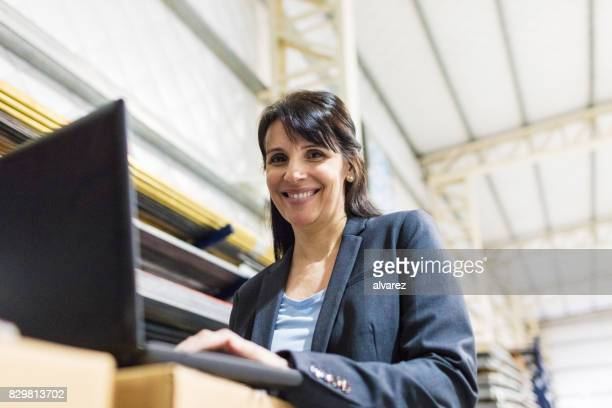 Businesswoman in manufacturing plant with laptop