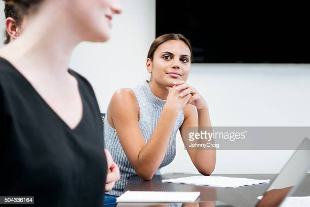 Businesswoman in meeting listening to colleague, hands on chin