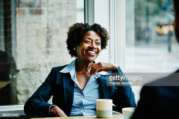 businesswoman in meeting with colleagues in cafe - leanincollection stock pictures, royalty-free photos & images