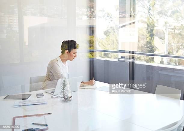 Businesswoman in meetingroom taking notes on paper
