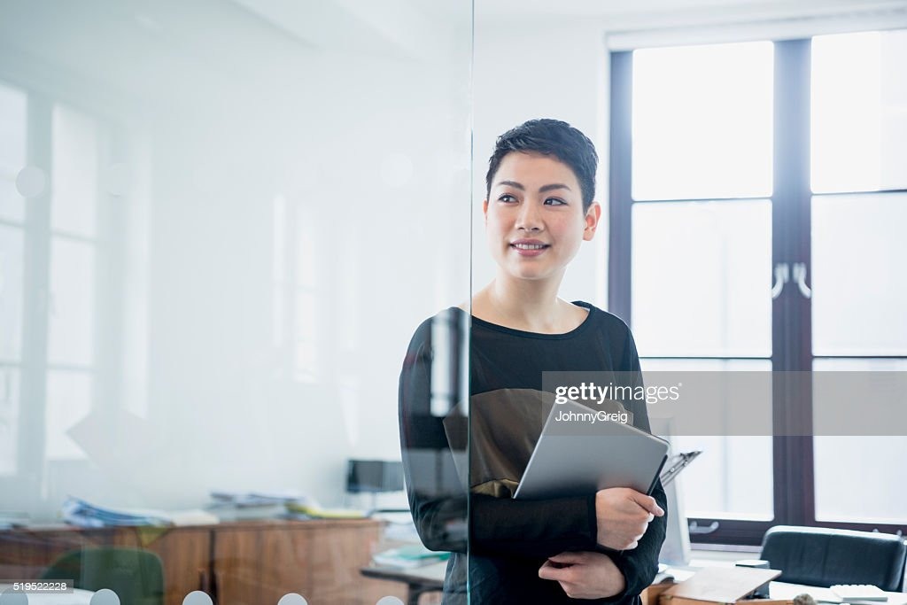 Businesswoman in modern office looking away through partition : Stock Photo