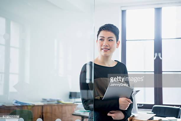 businesswoman in modern office looking away through partition - wegkijken stockfoto's en -beelden