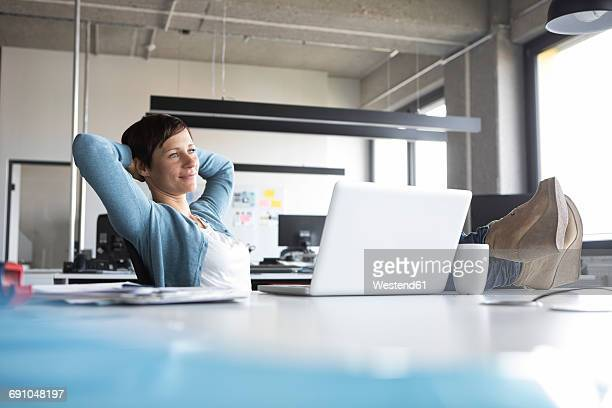 Businesswoman in office at desk relaxing